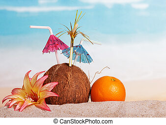 Coconut, orange and flower in the sand against sea. -...