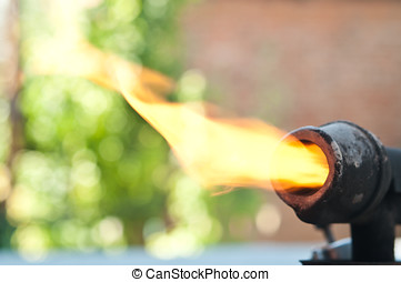 Old blowtorch with fire on background