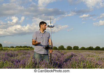 Land surveyor working in a lavender field and waiting for help