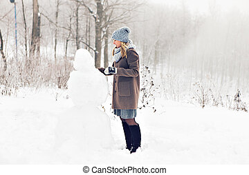 Woman making a snowman in winter time.