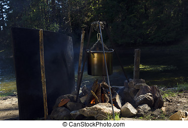 Camping fire in the wood next to lake