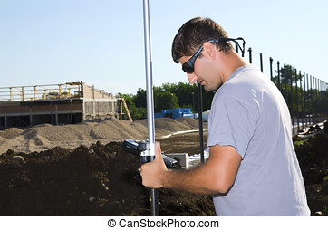 Geodesist working at a new village stadium