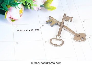 word wedding on calendar with sweet flowers and old key