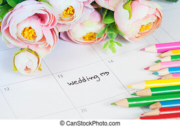 word wedding on calendar with sweet flowers and pen ,love...