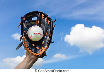 Hand holding baseball in glove with blue sky - Female hand...