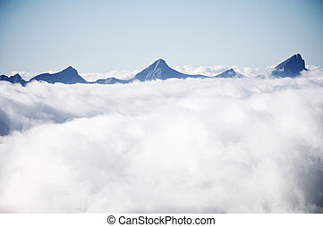 sea of clouds - pyramid shaped peaks and sea of clouds in...
