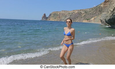 Slim attractive young woman in a blue bikini and sunglasses...