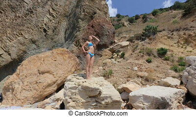 Seductive young woman with long hair in a blue bikini seductively moves standing on a rock
