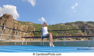 Gentle blonde in white dress sitting on a bench on the pleasure boat and enjoying
