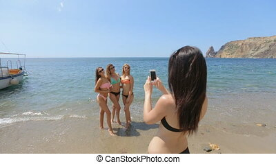 Girl photographing her friends in a bikini on the beach in...