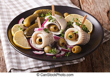 Tasty rollmops stuffed olives, onions, pickles and lemon...