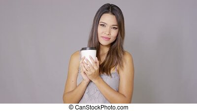 Attractive young woman drinking takeaway coffee from a...