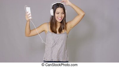 Rapturous young woman listening to music on her mobile phone...
