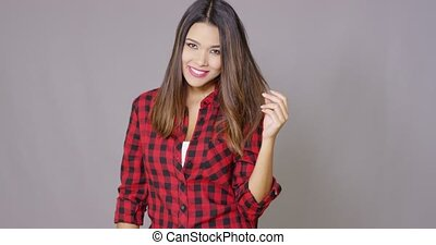 Single woman wearing checkered red and black shirt stands...
