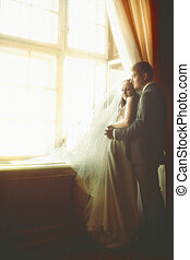 Couple daydreams in the sunlight while they look out of the...