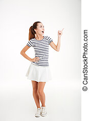 Cheerful young woman in skirt standing and pointing finger...
