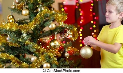 cute boy decorating christmas tree near the fireplace. Slow...