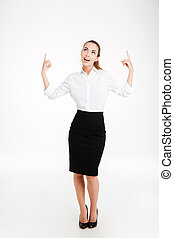 Portrait of a smiling young beautiful businesswoman pointing...