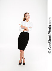 Cheerful young businesswoman pointing finger away and...