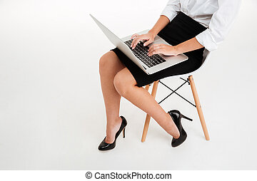 Cropped image of a businesswoman using laptop on the chair -...