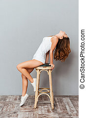 Portrait of a charming young woman posing on the chair...