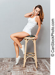 Portrait of a lovely young woman posing on the chair over...