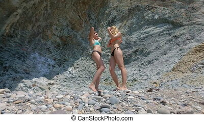 Two models in bikinis dancing on the background of rocks in...