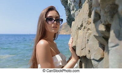 Sensual young woman with long straight hair in sunglasses...