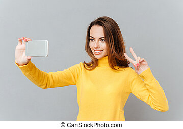Lovely playful young woman taking selfie with mobile phone -...