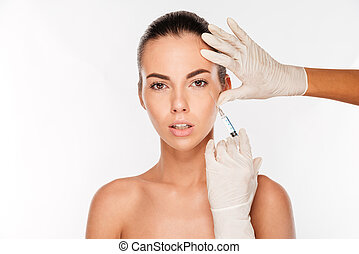 Beautiful woman gets an injection in her face isolated on...