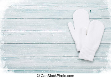 White mittens on wooden table. Christmas background. Top...