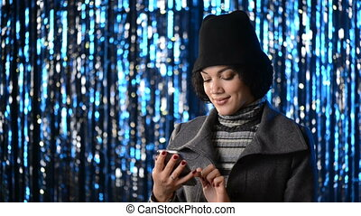 Smiling woman using her mobile phone over lights