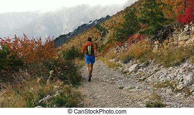 man runner running a mountain marathon in background of...