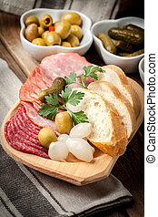 Tapas with sliced sausage, salami, olives, marinated onions,...