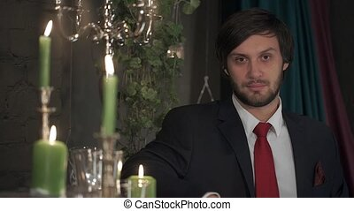 Portrait of brutal bearded man in a suit with a red tie in a romantic atmosphere by candlelight.