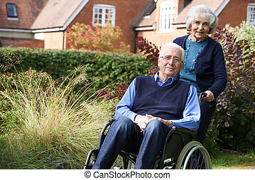 Senior Man Being Pushed By Wife In Wheelchair