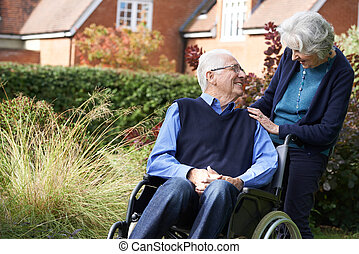 Senior Man Being Pushed In Wheelchair By Wife
