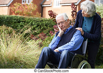 Depressed Depressed Senior Man In Wheelchair Being Pushed By...