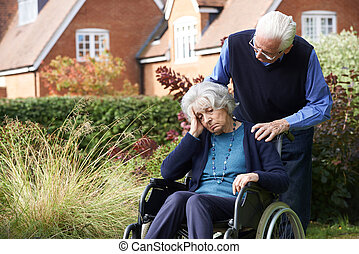 Depressed Senior Woman In Wheelchair Being Pushed By Husband