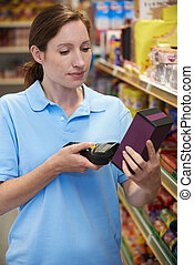 Sales Assistant Checking Stock Levels In Supmarket Using...
