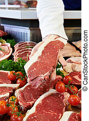 Butcher Showing Customer Sirloin Steak In Refrigerated...