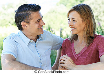 Smiling Mature Couple Talking To One Another Outdoors