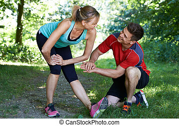 Mature Woman Exercising With Personal Trainer In Park