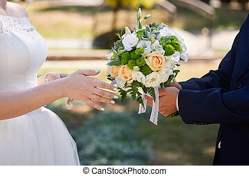 groom gives the bride a wedding bouquet. close-up of hands
