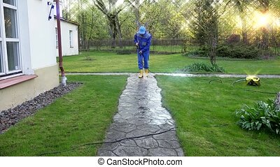Housekeeper guy washing concrete path near his house.
