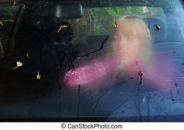 Sad Woman in the Car in the Fall - Blurry portrait of the...