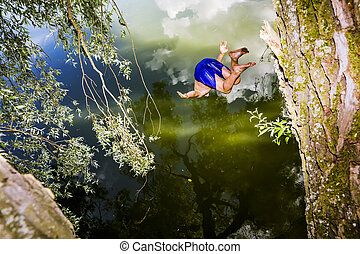 Men jumps in a lake with a bungee jumping
