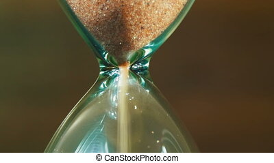 Sandglass on a Wooden Background, the Sand Falls Inside -...