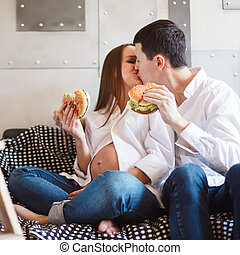 Pregnant couple eating fastfood and kissing