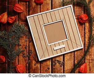 Photo frame stick on vintage wooden texture. Christmas and New Year background concept. Polaroid frames on retro style table. spruce branches, orange winter cherry and red bowtie